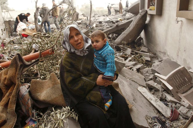A Palestinian woman sits on the rubble of her destroyed house after an Israeli air strike in Rafah in the southern Gaza Strip on 30 December, 2008