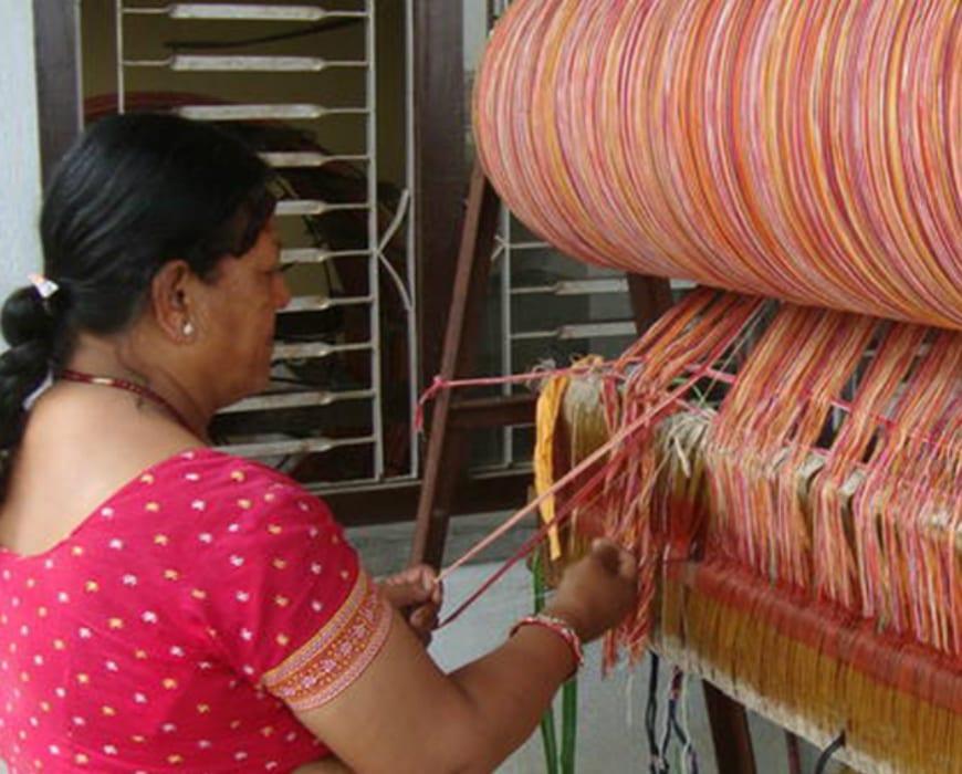 An artisan threading a loom
