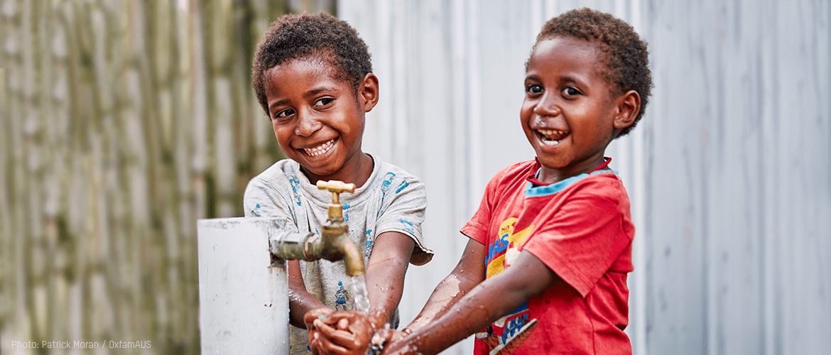 Goroka, Papua New Guinea: Mathilda and Malcolm with a newly installed tap during a vist by Oxfam to film scenes for the 2018 Comedy Gala.