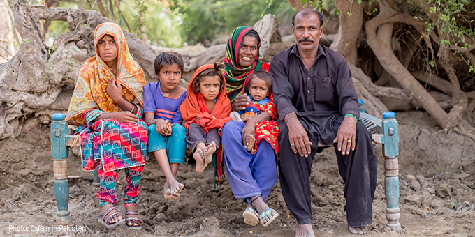 A family sit with their children against a backdrop of trees.
