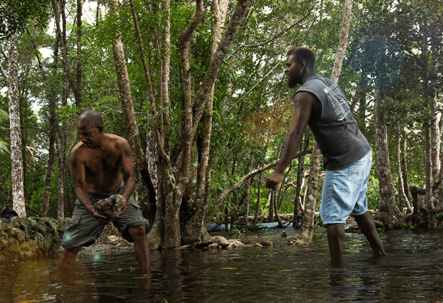 Two men shift buckets of water from a flooded stream.