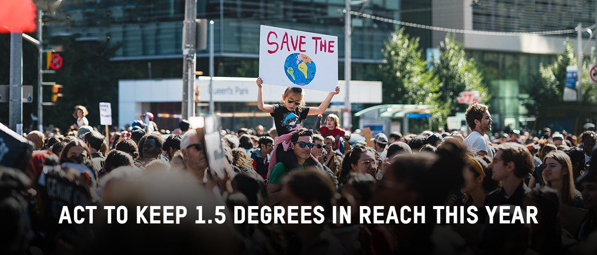 Image of a crowd protesting with test \Áct now to keep 1.5 degrees in reach